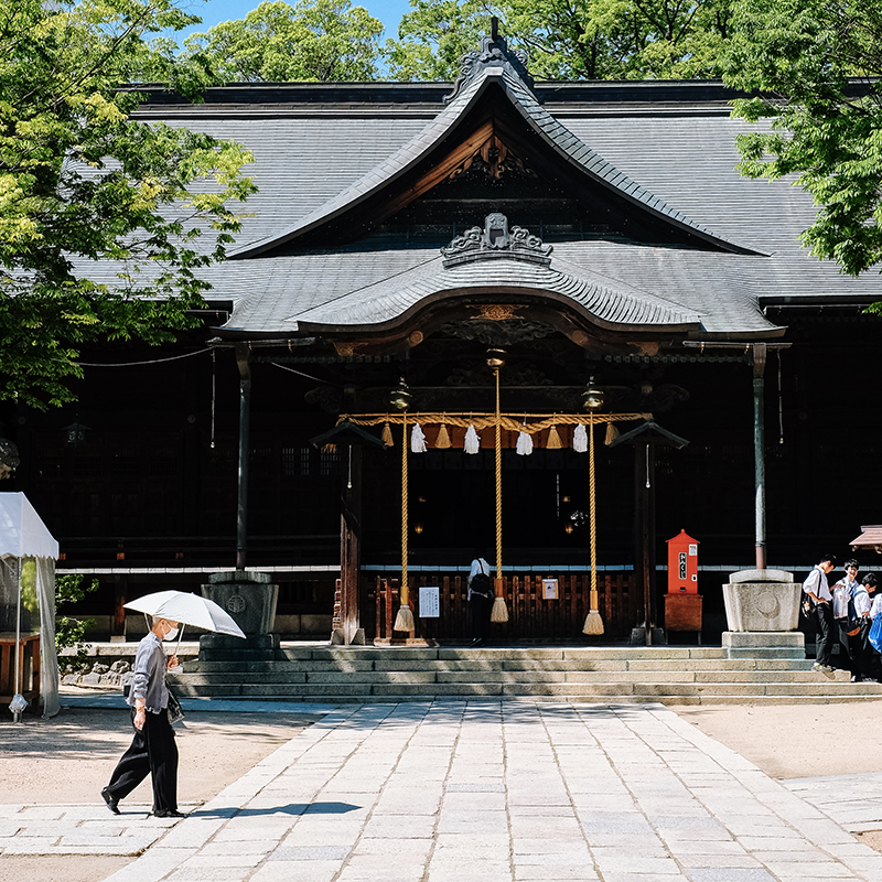 DAme âgée avec son ombrelle devant un temple à Matsumoto